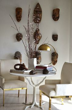 wooden masks | wall sculptures | dining room with white fabric chairs | interior design | home decor ideas | decoratin