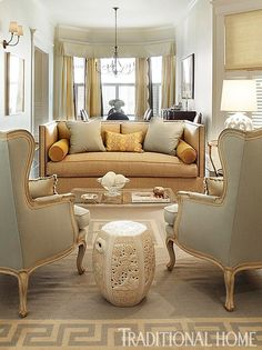 A sofa with clean lines and sand-colored upholstery faces a pair of curvy French armchairs in pale blue cotton. A rug with an oversized Greek-key pattern anchors the space. - Traditional Home ®/ Photo: Michal Venera / Design: Palmer Weiss