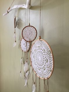 This beautiful wall hanging feathers 5 different size vintage doily dreamcatchers with clear crystal glitter tipped feathers on a beautiful piece of painted driftwood. Each piece created is unique and one of a kind, making it that little bit more special. Available in White