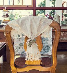 Ninguém diz que as flores são artificiais: amarradas ao jogo americano de tear, elas dão um toque delicado e romântico à cadeira rústica