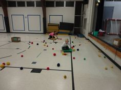 """December Games!  Pictures of Feed the Reindeer Relay - Students worked in groups of three. Each child had a turn to do each """"job"""". One child rode the sled (scooter) to collect reindeer food (balls). They tossed the reindeer food to the person standing inside the hula hoop and that person had to catch the food and throw it into the reindeer's bucket. The third child's job was to be the """"catcher"""" and try to help get the food into the buckets."""