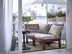 Een balkon met bruine houten stoel en hoekelement, met beige kussens en een zwarte ronde salontafel