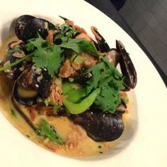 Thai-Style Mussels with Lemongrass Recipe Main Dishes with lemon, lemongrass, coconut milk, galangal, serrano chile, kaffir lime leaves, fine sea salt, freshly ground pepper, flavored oil, garlic, ginger, scallions, shallots, red chili peppers, mussels, thai basil, cilantro sprigs