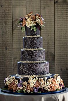 Brides.com: 22 Wedding Cakes for Dark, Modern Color Palettes. An Opulent, Five-Tier Wedding Cake. This five-tier custom chocolate fondant finished Ana Parzych Cakes wedding cake with sugar flowers is an ornate knockout! We're swooning over the bushed embroidery piping and gold dust detailing—not to mention borders of pressed lace fondant and hand-crafted sugar roses, calla lilies, freesias and orchids in burnt oranges, yellows and purples. Gorgeous! See more formal wedding cakes.