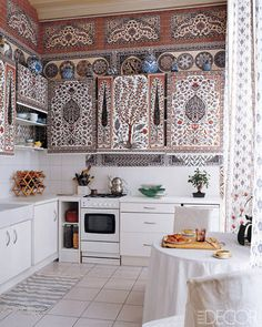 The Paris kitchen of Dimonah and Mehmet Iksel—who create exquisite wall coverings as Iksel Decorative Arts—features distinctive wallpaper and fabric from their firm; the open cabinets are concealed by custom-made rolling blinds. (December 2006)
