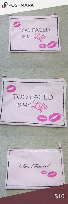 """Too Faced Is My Life Pink Kisses Makeup Zip Bag Too Faced brand. Pink with """"Too Faced Is My Life """" on the front and """"Too Faced """" on the other side with lip kisses. The top is zippered and is a great travel cosmetics bag. Used one time and washed. It is very packable and holds quite a bit. Smoke free home and fast shipping. Thank you for checking out my closet. Too Faced Bags"""