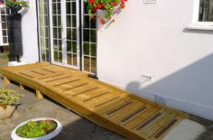 Wooden ramp access platform with non-slip decking strip areas.