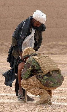 Prince Harry examines the leg of a local Afghan man as he tells him the route around a British Army cordon in the desert in Helmand Province