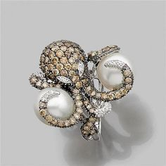 """Ring """"octopus"""" entirely paved with diamonds in shades of brown and yellow holding two cultured pearls. 18K white gold frame."""