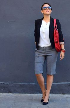 woman wearing bermuda shorts for office. she is wearing white blouse and black blazer and red bag