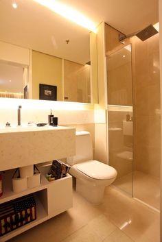 Banheiro com iluminação indireta, espelho com iluminação, mármore e tudo muito compacto. Projeto de Camila Klein