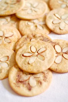 Sand Dollar Cookies 1/2 cup unsalted butter, softened 1 cup powdered sugar 2 large eggs - 1 whole, 1 yolk with the whole egg and the white in a separate bowl 1 teaspoon vanilla extract 1 pinch kosher salt 1 3/4 cup all-purpose flour 1/4 teaspoon baking powder Cinnamon sugar Sliced almonds