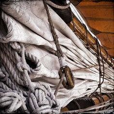 Close up of Rig and Sails on a Tall Ship in Michigan. sailing vessels employ two main types of rig: the square rig and the fore-and-aft rig and the sails of tall ships are attached to wooden timbers.