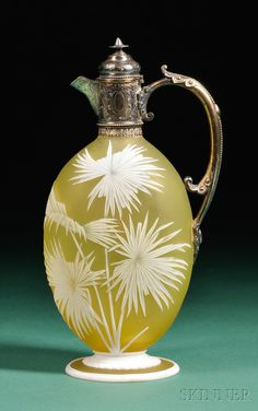 Thomas Webb and Sons Glass Claret Jug  Art glass and silver  England, c. 1885  The body decorated in white cameo glass with spiky-petaled flowers,  the reverse with a sheath of wheat and butterfly, on spreading foot decorated with white glass gadrooning on yellow ground, maker's mark on base, the mounting in silver-gilt by Frederick Bradford McCrea, London, 1885,.