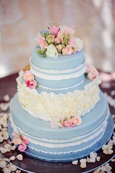 Bei dieser Idee aus einer babyblauen Torte gehören rosa Rosen dazu