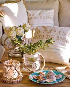 00386259B. Flores blancas, velas, conchas marinas y cojines blancos