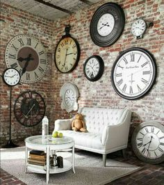 Big vintage cloacks on wall with cemented n concrete wall with comfy sofa gives u industrial n inspiring look