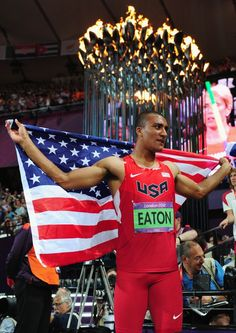 Ashton Eaton of the United States celebrates under the Olympic Cauldron after winning gold in the Men's Decathlon