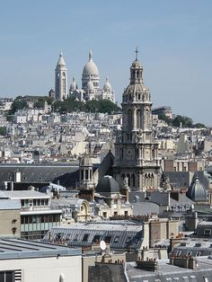 The Basilique du Sacré-Coeur de Montmartre from the terrace of the department store Le Printemps, Boulevard Haussmann, Paris 9th arr. In the foreground, the steeple of the church of the Holy Trinity.