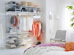 Dormitorio luminoso con estantes, cestos de rejilla y barras para ropa, todo en blanco.