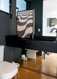 O espelho no lavabo amplia o ambiente. O efeito é potencializado porque ele também está na parte da bancada. Isso só foi possível com a bancada suspensa. Projeto do escritório Arqdonini