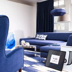 Inky blue living room with pendant to match! (not loving the plain wall though)