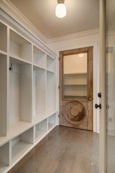 Beautiful mudroom features a wall of built-in lockers alongside a closet finished with a salvaged wood door