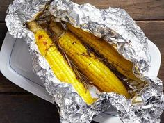 Foil-Packet Corn: Lay out 2 sheets of foil. Top each with 3 husked ears of corn, a sprig each of thyme, basil and rosemary, salt and pepper to taste, and 2 tablespoons cut-up butter. Fold into packets; crimp to seal. Wrap each packet in another sheet of foil. Grill over medium-high heat, 15 minutes per side