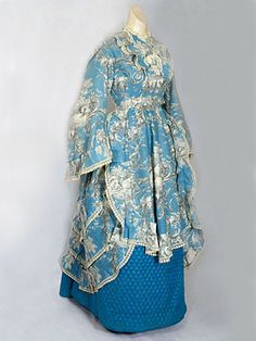 French toile bustle gown with quilted silk petticoat, c.1875. Amazing Victorian era clothing. I love blue, toile and quilted things, so this is an amazing dress to me. But the French velvet shoes are a close second...