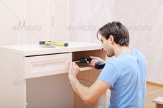 Buy repairer in assembly of furniture by photoshkolnik on PhotoDune. the repairer in assembly of furniture collects new furniture Hammer Drill, New Furniture, Stock Photos, Collection, Design, Author, Search, Searching