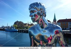 "Helsingor, Denmark - 06 May, 2018: Detail of sculpture ""Han"" of naked young man siting on stone gazing at sea by Michael Elmgrin and Ingar Dragset, Sculpture repeats pose of Mermaid in Copenhagen"