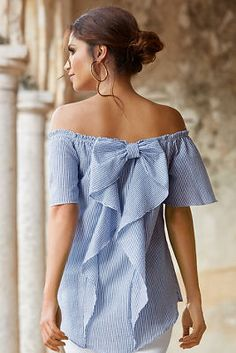 The sexy off-the-shoulder neckline teases to a romantic bow with ruffles that drape the back of this crepe textured, striped woven top styled in an effortless silhouette with