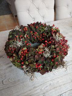 Hortensia, rozenbottels en wat gedroogde tillantsia, gestoken op een ring van steekschuim.