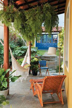 A varanda lateral pode ser estreita e ter colunas finas, mas deve ter muitas plantas para refrescar o entorno da casa
