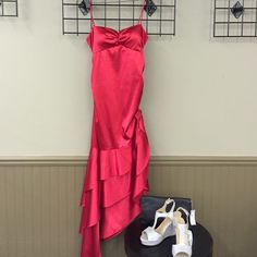 Thin Strap Asymmetrical Prom Gown True red thin strap slit bodice silky prom dress. Cinching on sides with rhinestone bow on one side. Asymmetrical bottom. Blondie Nites Dresses Prom