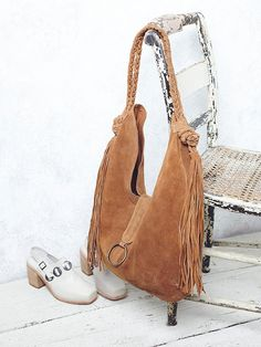 Bohemian Dreams Tote | In a super luxe suede, this hobo style bag features snakeskin print trim and statement fringe accents.  Braided handles with a lined interior that has zip and slip pockets.