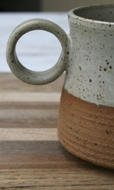 Rustic wheel thrown mug/coffee/tea cup from my new collection of functional ceramics designed to be sturdy for everyday use but with mindful creative elements to engage the user. The true beauty of the speckled stoneware clay is emphasized by placing contrasting raw unglazed clay against the matt gray/off white speckled glaze. I added some horizontal lines to the lower section to give the piece an interesting tactile texture against the smoothness of the glaze. The handle is a modern circle…