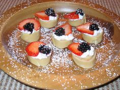 Crepe Bites - Crepes spread with a mixture of whipped cream and strawberries. Rolled, cut, and topped with a strawberry slice and a halved blackberry.