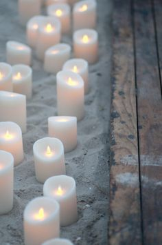 In the sand along the runner (here its driftwood but I also like the idea of planks or stones), light tapered or thick white candles