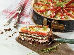 Geschichtete Schwarzbrottorte mit Schinken- und Käsefüllung und einem Topping aus Tomaten und Ei.