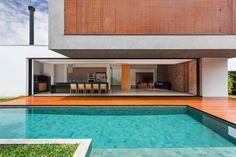 Com grandes portas de correr que ficam embutidas nas paredes, os arquitetos do CF Arquitetura priorizaram a integração dos ambientes