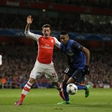 Arsenal's Mesut Ozil, left, challenges Monaco's Wallace during the Champions League round of 16 soccer match between Arsenal and AS Monaco at the Emirates Stadium in London, Wednesday, Feb. 25, 2015.  (AP Photo/Matt Dunham)