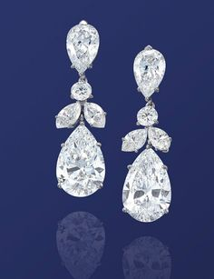 AN IMPORTANT PAIR OF DIAMOND EAR PENDANTS  Each set with a pear-shaped diamond weighing 5.24 and 5.20 carats, suspended from a pear-shaped diamond surmount weighing 1.71 and 1.46 carats, joined to the trefoil brilliant and marquise-cut diamond spacer, mounted in platinum, 3.6 cm long