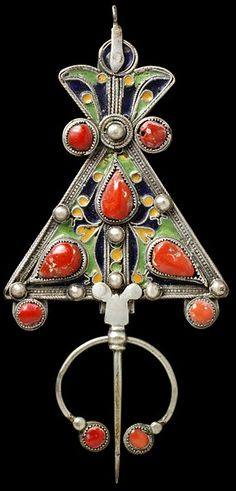 This silver shoulder brooch would have been worn by Kabyle women in the first half of the nineteenth century to affix their robes. The Kabyles are a Berber people from the Atlas mountains in North Eastern Algeria. Silver, enamel, coral, Algeria, 1800-1893