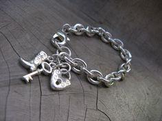 Pulsera en plata con eslabones y detalle de llave, bota, corazón.