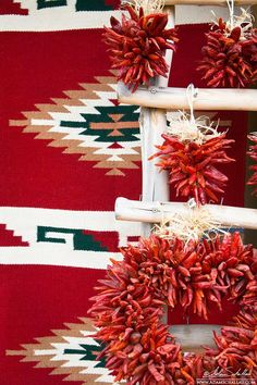 Chile ristras hung on a pueblo ladder in front of a Native American Indian blanket. Taos, New Mexico. Photo by Adam Schallau.