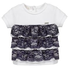 Baby girls white top with lace by Liu Jo. Made in soft cotton jersey, this pretty design has blue lace frill details at the front, with popper fastening at the back of the neck and a logo metal plate stitched on the chest.