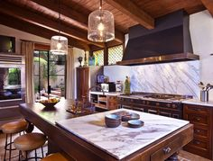 Dark, rich, masculine kitchen- great look. And I LOVE the white marble!