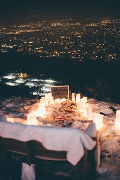 Now that's a dreamy proposal setup. Candles, snow, and a perfect view of the city lights!