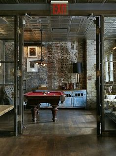 I love the look of the unfinished yet finished basement. games room with exposed brick walls and a pool table